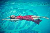 Young sexy woman floating on swimming pool in red dress. beauty shot — Stock Photo