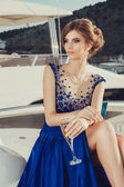 Beautiful young sexy girl in a dress and makeup, summer trip on a yacht with white sails on the sea or ocean — Foto Stock