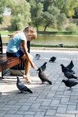 Girl feeding pigeons in the park — Stock Photo