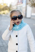 Smiling little girl in talking on cell phone — Stock Photo
