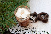 Cup of hot chocolate with marshmallows, cakes and fir branches. — Foto de Stock