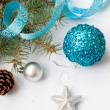 Branch of a Christmas tree and blue ball and ribbon — Stock Photo #59939427
