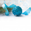 Branch of a Christmas tree and blue ball and ribbon — Stock Photo #59943909