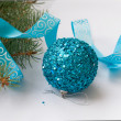 Branch of a Christmas tree and blue ball and ribbon — Stock Photo #59943963