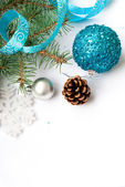 Branch of a Christmas tree and blue ball and ribbon — Stock Photo