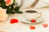 Cup of coffee, sugar hearts and a bouquet of cream roses — Stock Photo