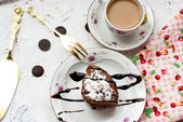 Piece of chocolate cake and a cup of coffee with milk — Stock Photo