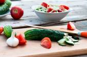 Chopped cucumber and tomato salad on a cutting board — Stock Photo