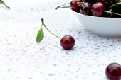 Single cherry and a plate of cherries — Stock Photo