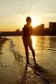 Young woman on a beach at sunset — Stock Photo