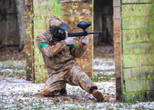 Extreme sportsman playing paintball game on first snow — Stock Photo