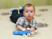 Very surprised baby boy lying on the bed — Stock Photo