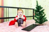 Pleased baby in new year suit with tablet computer — Stock Photo