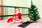 Funny toddler in new year suit picks his nose on the bed — Stock Photo