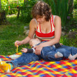 Mother feeds child on bright plaid outdoors — Stock Photo #60674373
