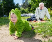 Child creeps away from grandfather outdoors — Stock Photo