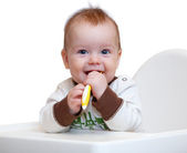 Smiling baby with spoon in his hands — Stock Photo