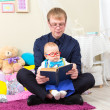 Serious little boy read an old book with his father in glasses — Stock Photo #69433353