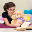 Serious girl and teddy bear reading a book in glasses — Stock Photo #69433451