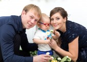 Happy family with one year old boy with flowers — Stock Photo