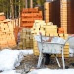 Wheelbarrow and bricks near fence — Stock Photo #71189369