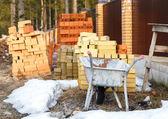 Wheelbarrow and bricks near fence — Stock Photo