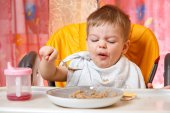 Funny  baby with grimace holds  spoon with buckwheat cereal — Stock Photo