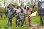 Team of five men with flag play paintball — Stockfoto