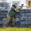 Paintball sportsman standing behind tires and shooting — Stock Photo #78369666