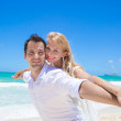 Cheerful couple having fun at the beach on a sunny day — Stock Photo #52089233