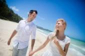 Happy couple walking on beach. — Stock Photo