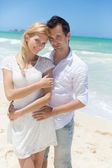 Cheerful couple embracing and posing on the beach on a sunny day — Stock Photo
