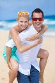 Happy young couple enjoying a solitary beach backriding — Stock Photo