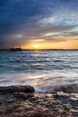 Wonderful solar Red Sea beach at a luxury hotel, at sunset. Sharm El Sheikh, Sinai, Egypt. Gold sunset with mountains and big wave. — Stock Photo