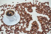 Cup of coffee and beans on beige background with human — Stock Photo