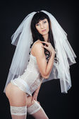 Sexy beautiful nude bride with veil in white erotic lingerie on a black background. beauty portrait of woman — Zdjęcie stockowe
