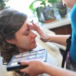 Woman applying make up for bride in her wedding day near mirror. Closeup of makeup artist — Stock Photo #71344057