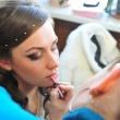 Woman applying make up for bride in her wedding day near mirror. Closeup of makeup artist — Stock Photo #71345237