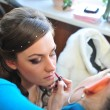 Woman applying make up for bride in her wedding day near mirror. Closeup of makeup artist — Stock Photo #71345321