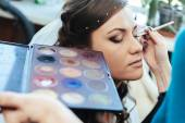 Woman applying make up for bride in her wedding day near mirror. Closeup of makeup artist — Stock Photo