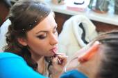 Woman applying make up for bride in her wedding day near mirror. Closeup of makeup artist — Fotografia Stock