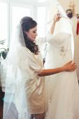 Happy beautiful bride tries on a wedding dress dressing gown. Girl have final preparation for wedding. Beautiful newlywed woman with long hair — Stock Photo