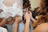 Bridesmaid is helping the bride tying bow on wedding dress. — Stock Photo