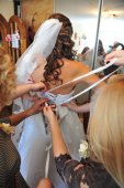 Bridesmaid is helping the bride tying bow on wedding dress. — Fotografia Stock