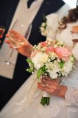 Wedding bouquet of flowers, close up. Young wedding couple indoors portrait. — Foto Stock