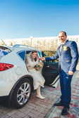 Bride and groom near vintage decorated car on wedding day. — Stock Photo