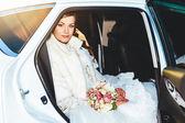 Close-up portrait of pretty shy bride in a car window — Stock Photo