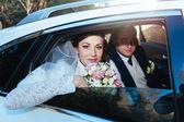 Portrait of happy bride and groom in the car. — Zdjęcie stockowe