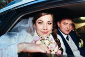 Portrait of happy bride and groom in the car. — Stock Photo