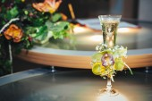 Wedding bouquet and champagne glass with flowers — Stock Photo